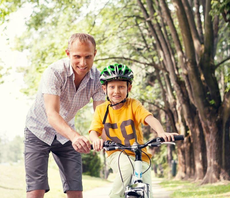 Fadern lär hans son för att rida bicykle royaltyfri fotografi