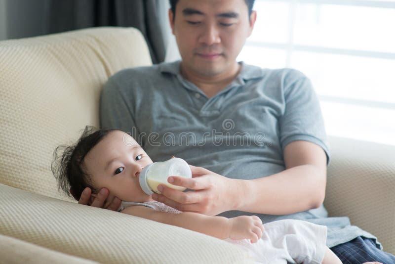 Fadern matar med flaska mjölkar för att behandla som ett barn fotografering för bildbyråer