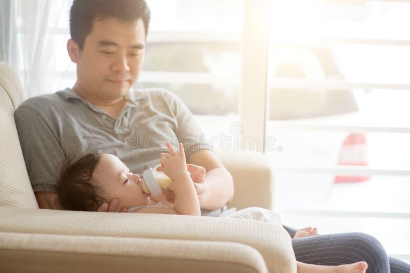 Fadern matar med flaska mjölkar till lilla barnet royaltyfri bild