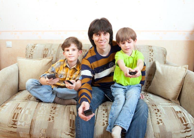 Fadern med barn sitter på soffan royaltyfri foto