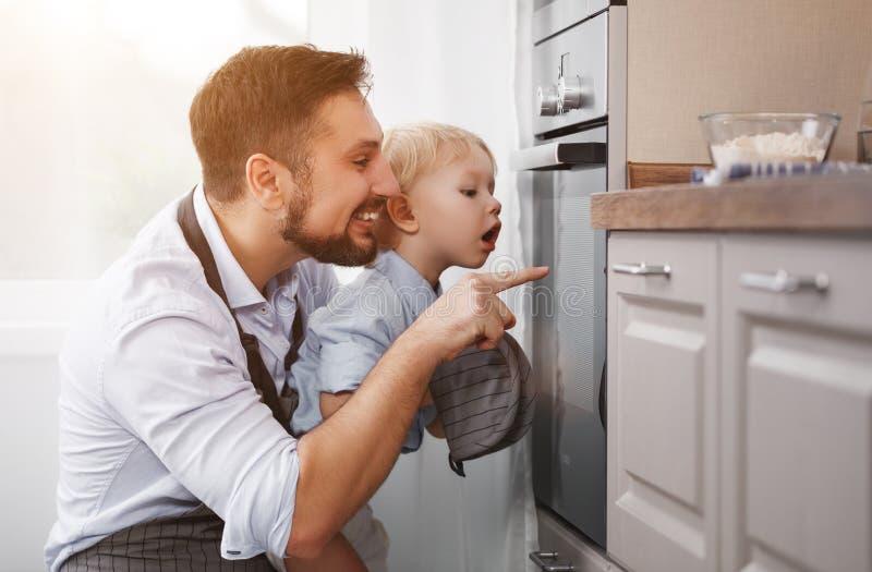 Fadern med barnsonen förbereder mål, bakar kakor royaltyfri bild