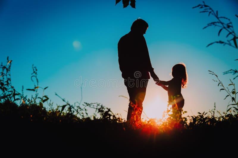 Fadern med den lilla dottern går på solnedgången royaltyfria foton