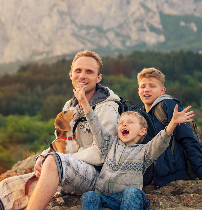 Fadern med söner och den favorit- valpen på berget går arkivbilder