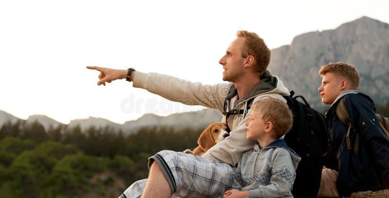 Fadern med söner på berget går arkivfoto