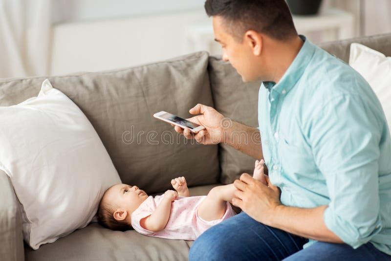 Fadern med smartphonen som tar bilden, behandla som ett barn hemma royaltyfri foto