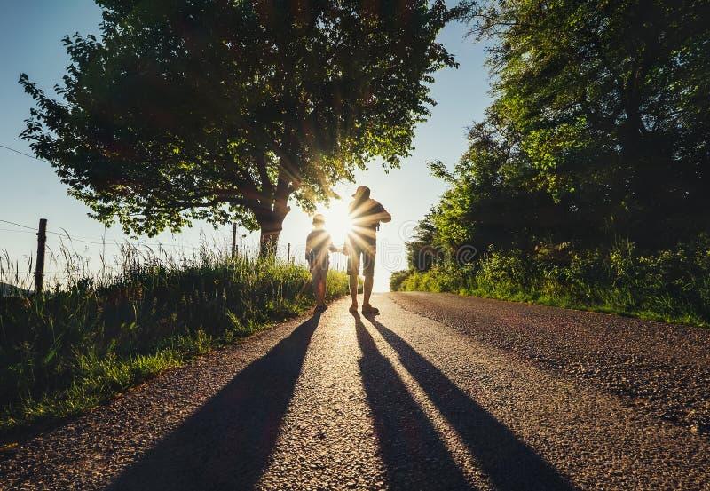 Fadern med sonen går tillsammans på solnedgångvägen arkivfoto