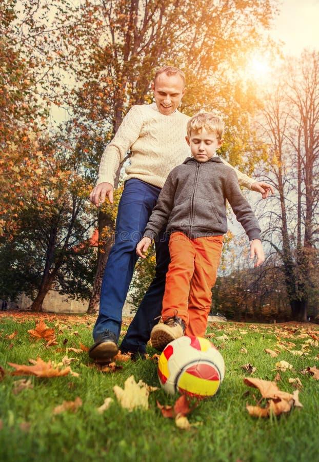 Fadern med sonen som spelar i fotboll på hösten, parkerar arkivbilder