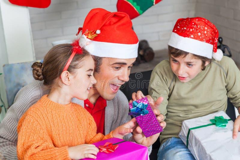 Fadern med två ungar öppnar julgåvor royaltyfria bilder