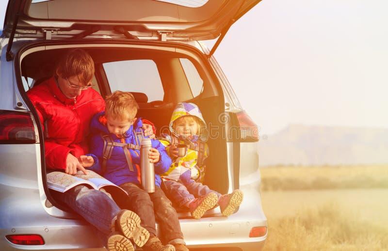 Fadern med ungar reser med bilen i berg royaltyfri fotografi