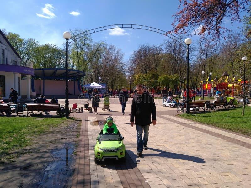 Fadern medföljer en son som rider en bil för barn` s i extraförmåner fotografering för bildbyråer