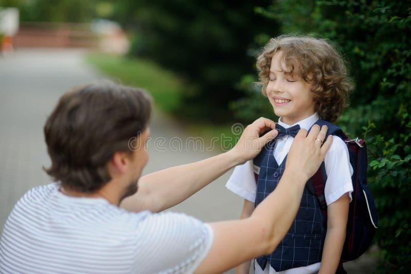 Fadern medföljer hans son-väghyvel till skolan arkivfoton