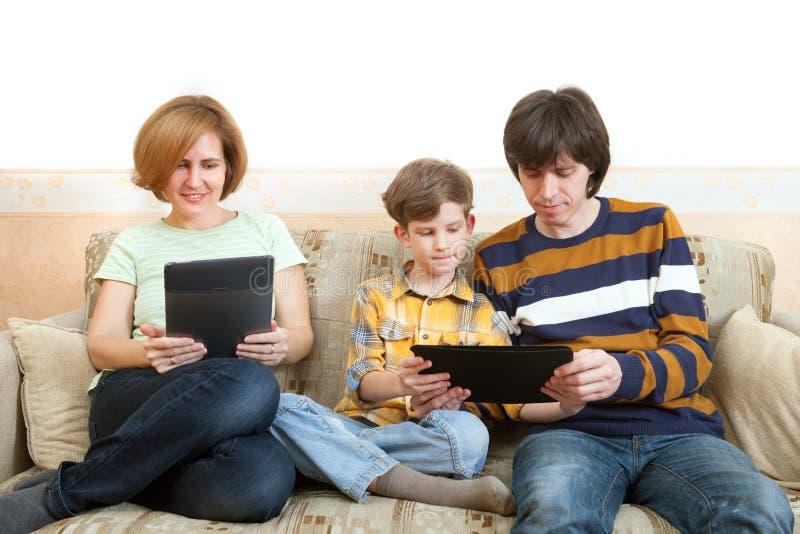 Fadern, modern och sonen sitter med elektroniska apparater royaltyfria foton