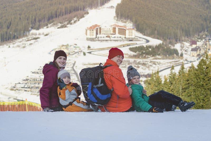 Fadern, modern och två barn sitter och ler på bakgrunden av skidar semesterorten Solig dag för vinter royaltyfria foton