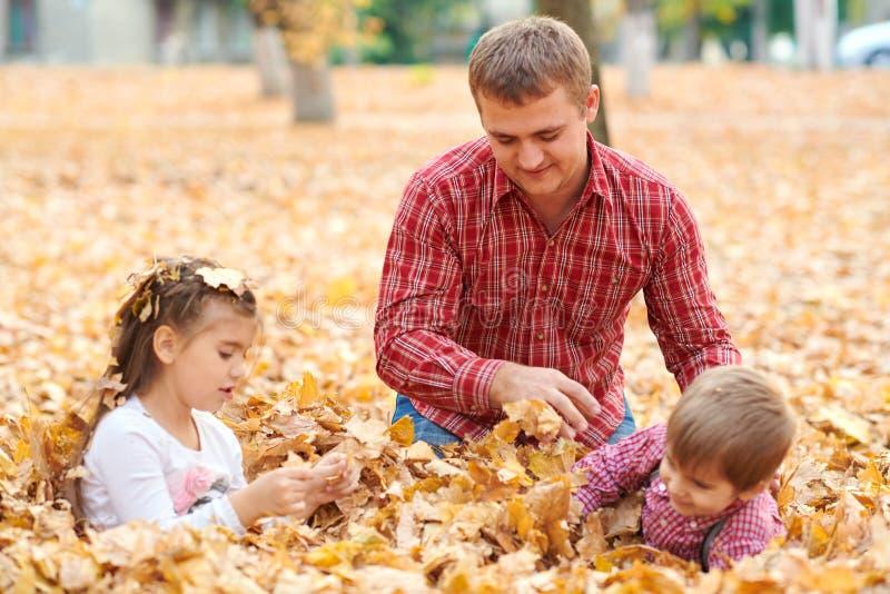 Fadern och barn ligger på gula sidor, och ha gyckel i höststad parkera Dem som poserar, le som spelar Ljus gul tr arkivfoto