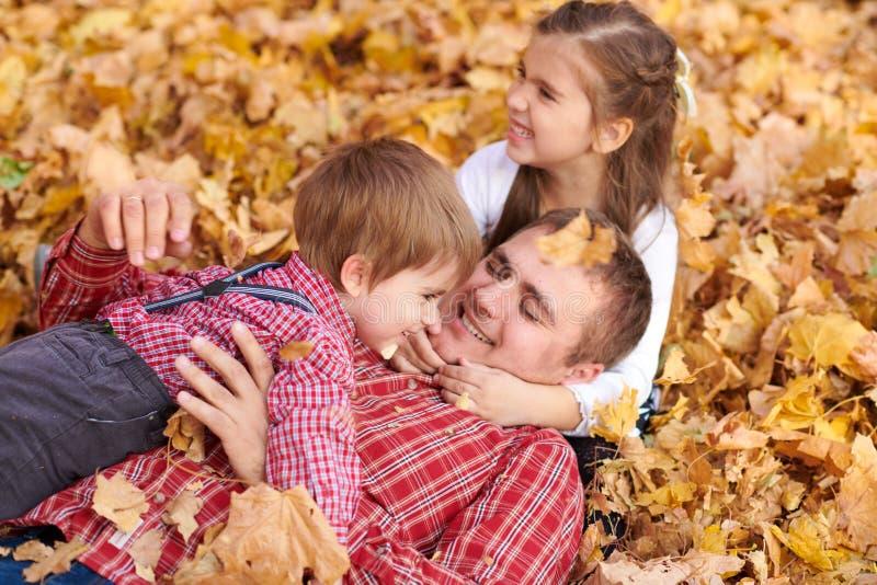 Fadern och barn ligger på gula sidor, och ha gyckel i höststad parkera Dem som poserar, le som spelar Ljus gul tr arkivbild