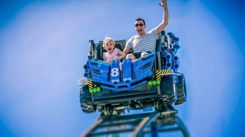 Fadern och barndottern som skriker med armar, lyftte på berg-och dalbanan i Florida, USA fotografering för bildbyråer