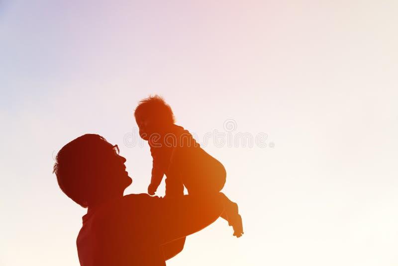 Fadern och behandla som ett barn lite konturer spelar på himmel royaltyfri fotografi