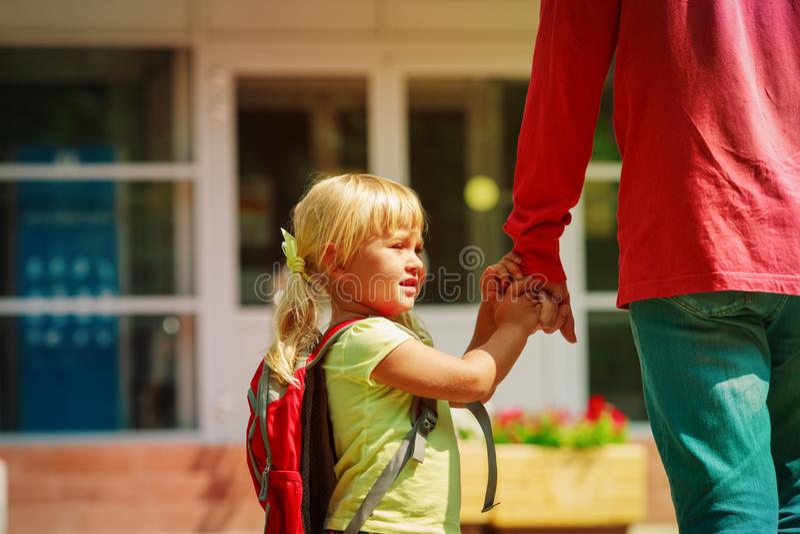 Fadern och den lilla dottern går till skolan eller daycare royaltyfria foton