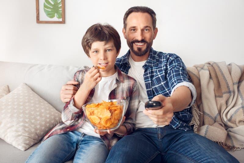 Fadern och den lilla sonen som sitter på soffapojken som äter hållande ögonen på tv för chipen, koncentrerade hemma farsan som ko arkivbilder