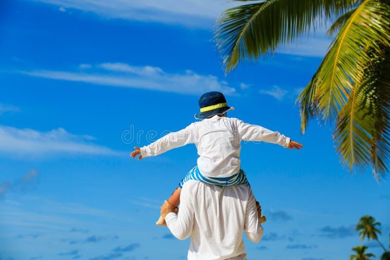Fadern och den lilla sonen spelar på himmel på tropiskt arkivbilder