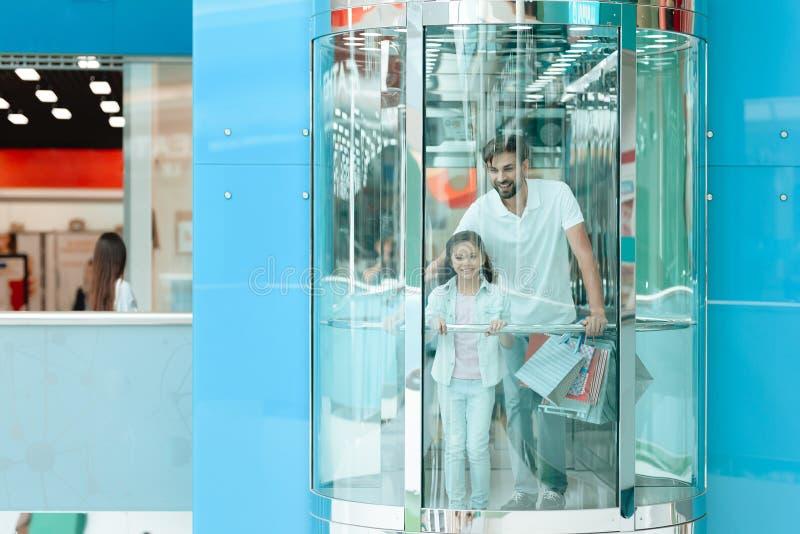 Fadern och dottern går ner i hiss i shoppinggalleria fotografering för bildbyråer