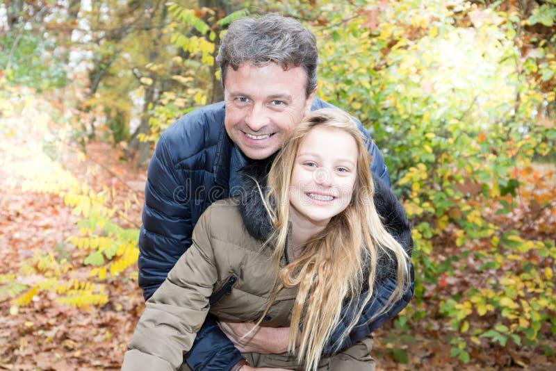 Fadern och dottern i hösten parkerar lek som skrattar den nätta blonda flickan, kramar hennes farsa royaltyfri foto