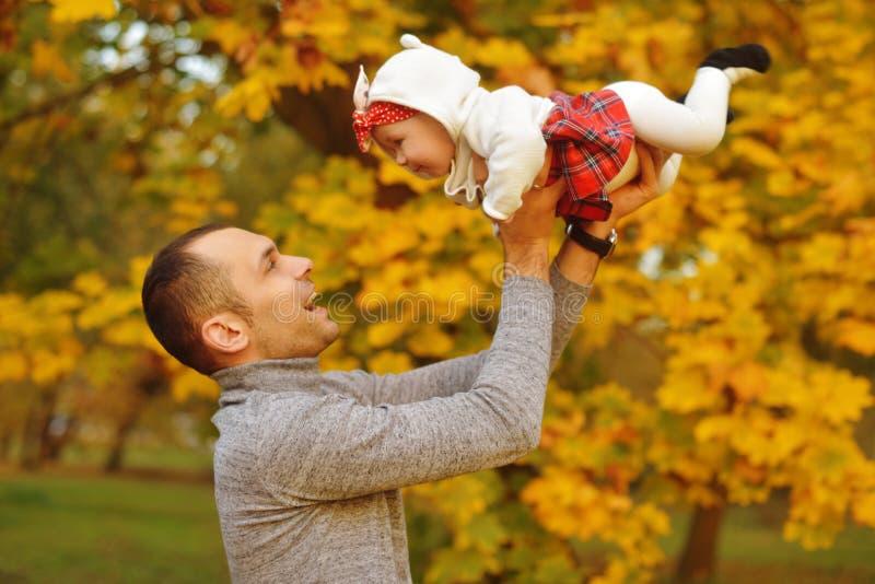 Fadern och dottern på stupade sidor för hösten i parkerar och att tycka om en härlig höstdag Lycklig glad ung familjfader arkivfoton