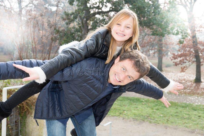 Fadern och dottern som har en rolig ridtur på axlarna i höstvinter, parkerar familjen royaltyfria bilder
