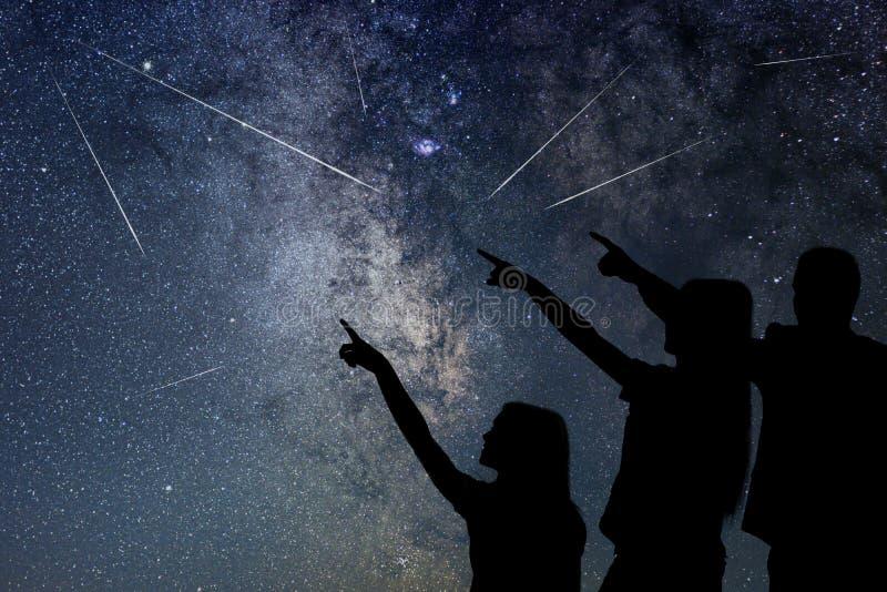 Fadern och hans dotter håller ögonen på meteorregnet sky för natt för abstraktionillustrationblixt arkivbilder