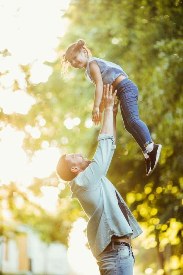 Fadern och hans dotter spelar med henne i luften i sommar parkerar utomhus på solnedgång arkivbilder