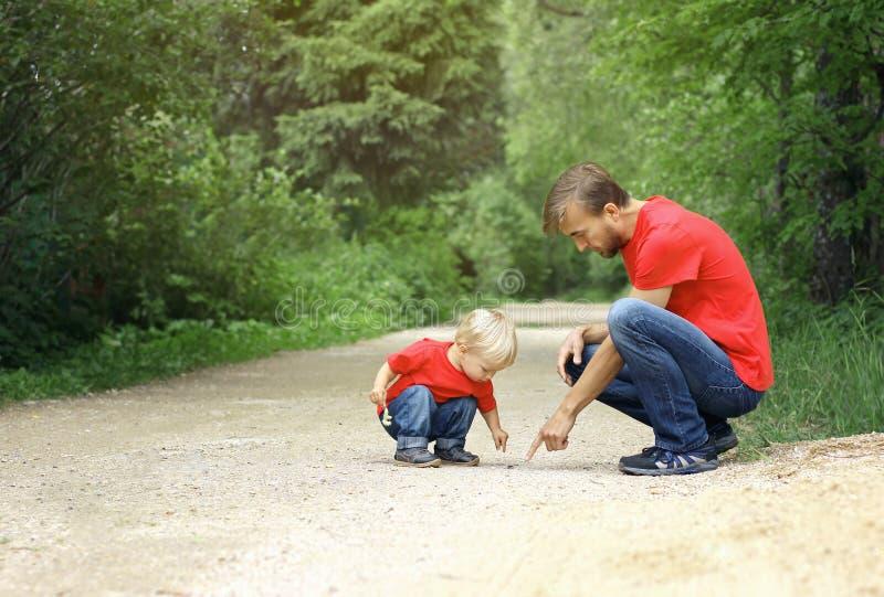 Fadern och hans litet barnson grundar krypet och kontrollerar det Undersökande naturbegrepp för unge kopiera avstånd royaltyfri bild