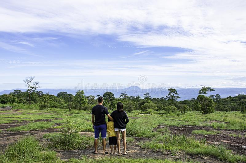 Fadern och modern kramade deras son och såg bergen och träden på den Phu Hin Rong Kla nationalparken, Phetchabun in royaltyfri foto