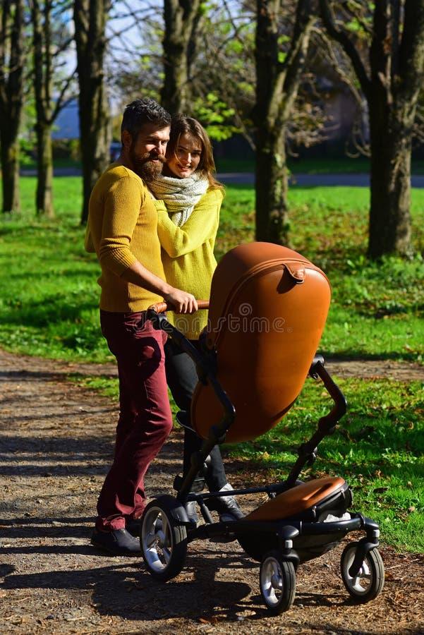 Fadern och modern med behandla som ett barn sittvagnen, familjbindning Lyckliga föräldrar går i höst parkerar utomhus- Begrepp fö arkivbilder