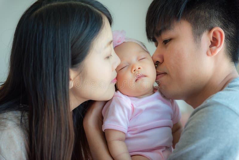 Fadern och modern som lite kysser, behandla som ett barn, föräldraskap, den conc familjen royaltyfria foton