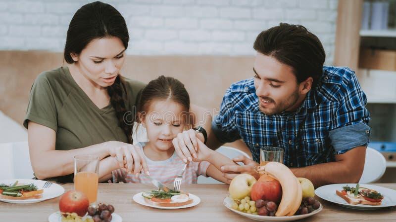 Fadern och modern undervisar lilla flickan äter bestick royaltyfri fotografi