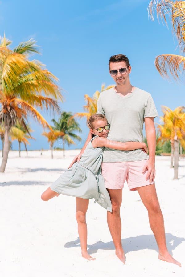 Fadern och sm? flickor har mycket gyckel p? den vita sandiga stranden arkivfoton