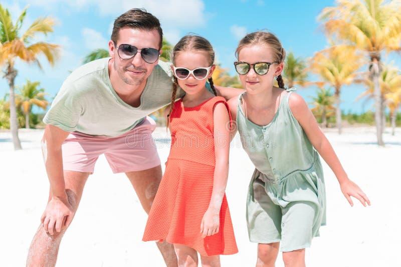 Fadern och sm? flickor har mycket gyckel p? den vita sandiga stranden royaltyfri bild
