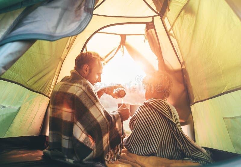 Fadern och sonen dricker varmt te som tillsammans sitter i campa t?lt royaltyfria bilder