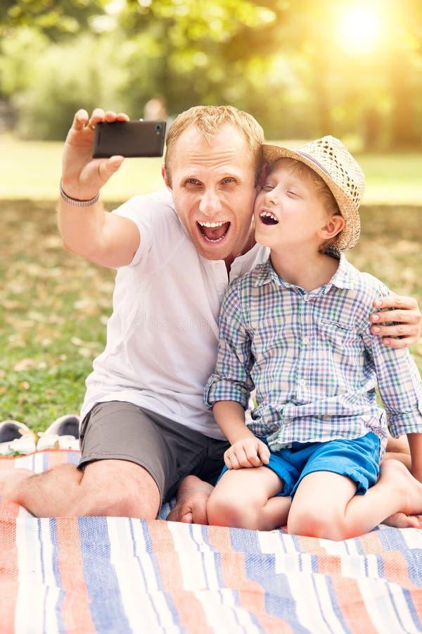 Fadern och sonen gör ett självfoto i sommar att parkera fotografering för bildbyråer