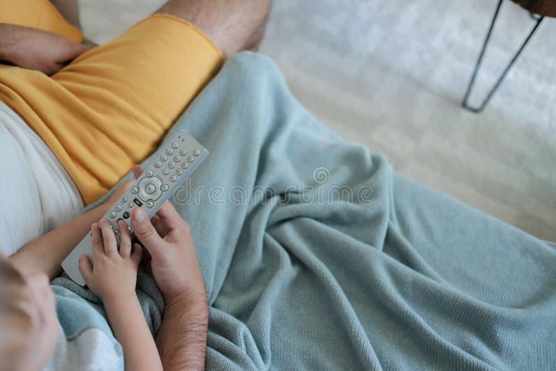 Fadern och sonen håller ögonen på tv tillsammans och att rymma fjärrkontrollen i deras händer, mysig hem- atmosfär royaltyfri bild