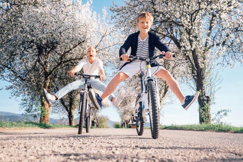Fadern och sonen har en gyckel, när att rida cyklar på landsväg w royaltyfri fotografi