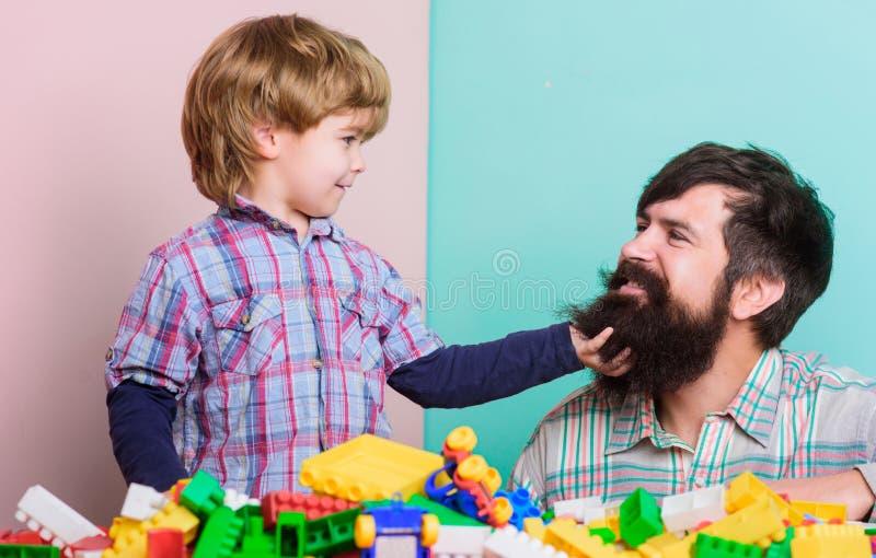 Fadern och sonen har gyckel med tegelstenar Barns utveckling och uppfostran Sk?ggig hipster- och pojkelek tillsammans Farsa och fotografering för bildbyråer