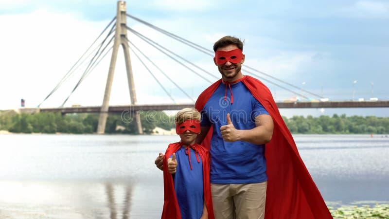 Fadern och sonen i superhero kostymerar visningtummar upp, motivation och teamwork royaltyfria foton