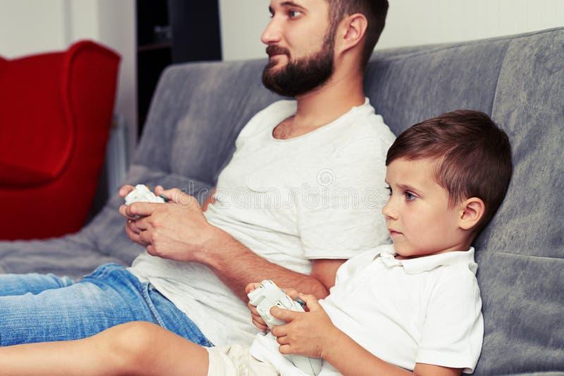 Fadern och sonen koncentrerade på att spela använda för videogame som var joystic arkivfoto