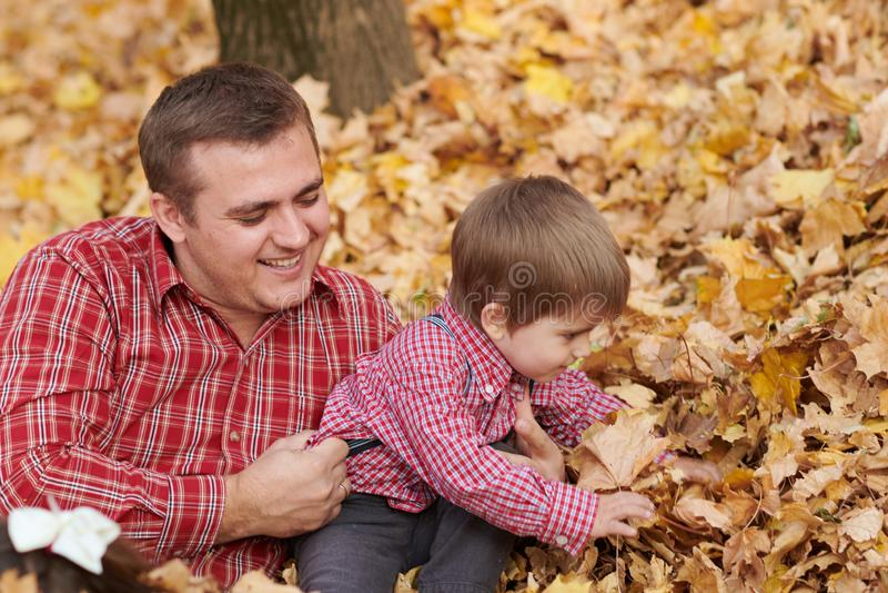 Fadern och sonen ligger på gula sidor, och ha gyckel i höststad parkera Dem som poserar, le som spelar Ljusa gula träd arkivfoto