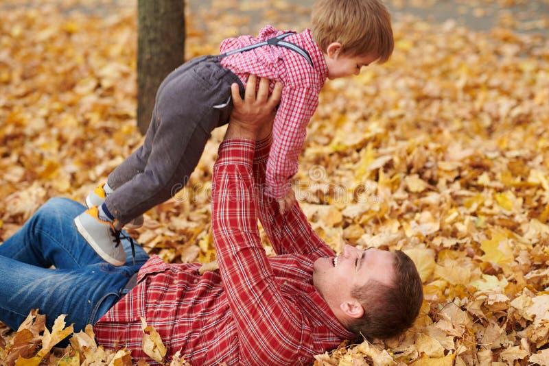 Fadern och sonen ligger på gula sidor, och ha gyckel i höststad parkera Dem som poserar, le som spelar Ljusa gula träd arkivbilder