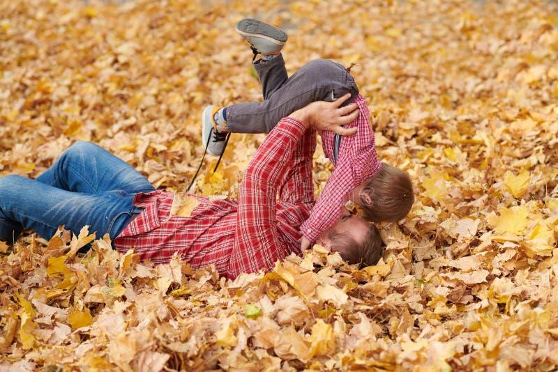 Fadern och sonen ligger på gula sidor, och ha gyckel i höststad parkera Dem som poserar, le som spelar Ljusa gula träd fotografering för bildbyråer
