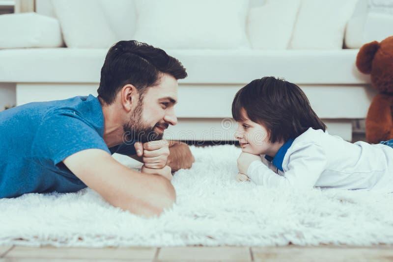 Fadern och sonen ligger på matta royaltyfria bilder