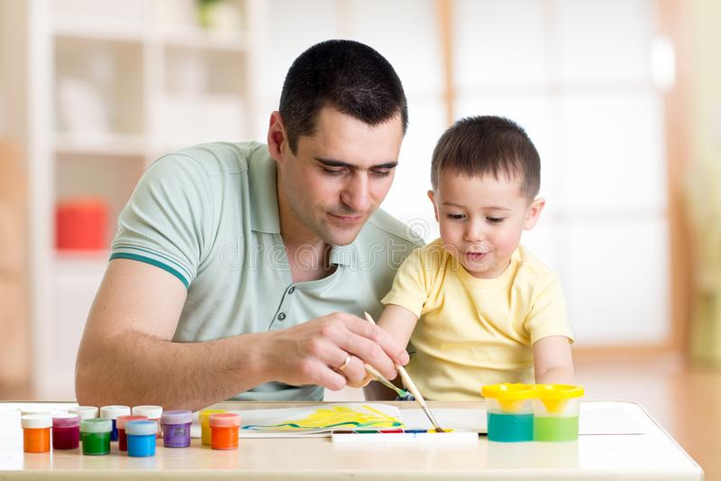 Fadern och sonen målar tillsammans Den lyckliga familjen färgar med målarpenseln Mannen och barnet har en rolig tidsfördriv royaltyfri bild
