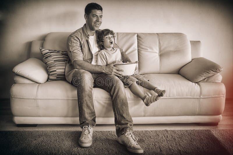 Fadern och sonen med popcorn bowlar hållande ögonen på tv i vardagsrummet arkivfoto